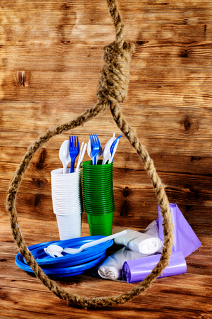 A disposable tableware in a rope loop, the concept of human dependence on disposable tableware. Environmental pollution with plastic and polymer waste