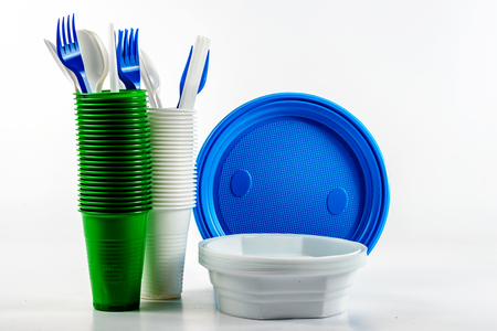 The bright plastic disposable tableware on white background, the concept of conservation. Plastic recycling Imagens