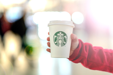 The child is holding a cup of Starbucks drink against the blurry lights of a shopping center. Russian Federation, Rostov-on-Don, April 12 Editorial
