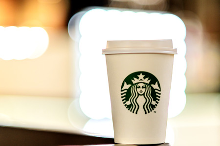 A white paper cup with coffee from Starbucks against the background of the blurry lights of the shopping center.  Russian Federation, Rostov-on-Don, April 13 Editorial