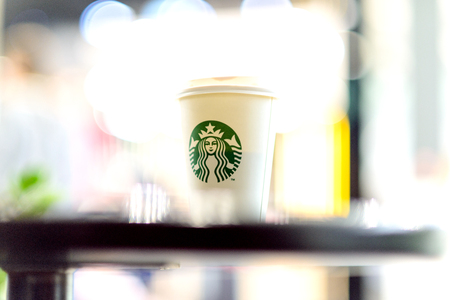 A white paper cup with coffee from Starbucks against the background of the blurry lights of the shopping center.  Russian Federation, Rostov-on-Don, April 12 Editorial