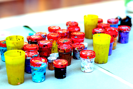 A jars of paint, with paint stains on a white sheet of paper. Colorful gouache paints in jars.