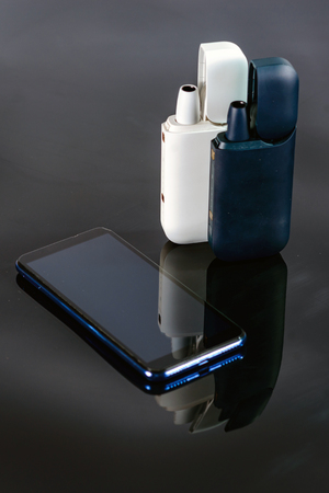 The devices for heating  tobacco cigarettes  with a charger. Charger it's a case . The smartphone  located next to charge on a black mirror background