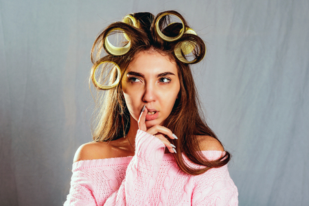 The portrait beautiful girl with curlers in her hair and a pink knitted sweater, isolated  on grey