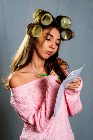 The portrait of a cheerful young woman with rollers in her hair. wearing  pink sweater standing isolated over gray background, writing notes on a sheet Imagens
