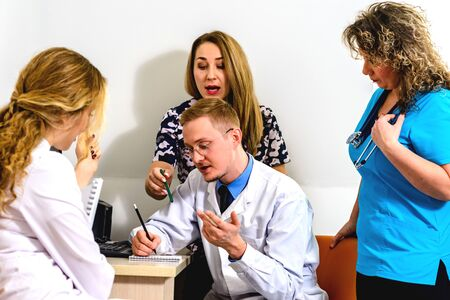 A group of young doctors with a mature mentor are discussing something standing around a young doctor with glasses