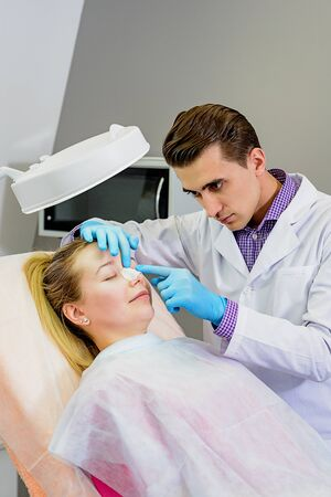 Male doctor preparing a mold of the curve of the nose the patient is female, to follow the alignment procedure of the nose. Rena Therme Hartman for plastic surgery.