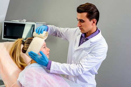 The doctor applies an elastic bandage on the patients head preventing excessive swelling of the face after plastic surgery. Wrinkle smoothing procedure Stock Photo