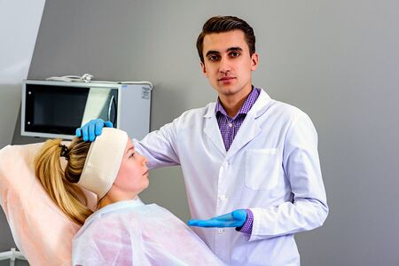 The doctor applies an elastic bandage on the patients head preventing excessive swelling of the face after plastic surgery. Wrinkle smoothing procedure Фото со стока