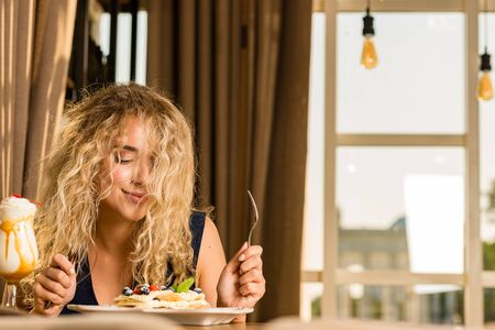 The girl is happy brought dessert, anticipating the delicious taste of delicate cake. Stock Photo