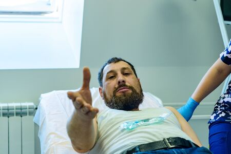 A man with a beard is lying on a hospital bed and with a hope in eyes reach out his hand forward, hoping to get help from people