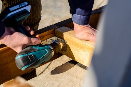 The photo shows the hands of the master, close-up. Master holds a portable screwdriver for screwing screws into the wood board, using metal corners Stock Photo