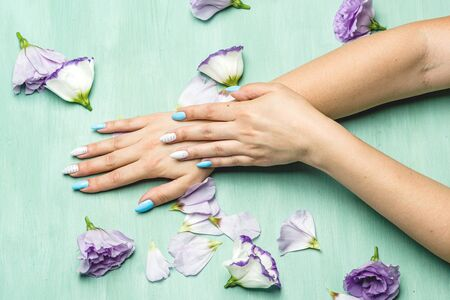female hands lie on a green background next to flower petals and flowers