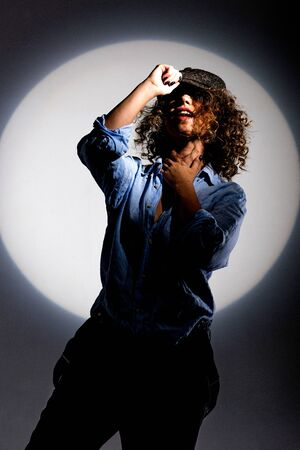 Girl with curly hair in a beam of bright light (gobo mask) in a linen blue shirt on a white background Standard-Bild - 138033083