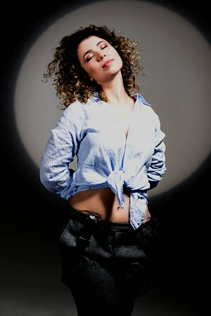 Girl with curly hair in a beam of bright light (gobo mask) in a linen blue shirt on a white background