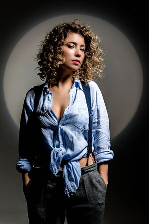 Girl with curly hair in a beam of bright light (gobo mask) in a linen blue shirt on a white background Standard-Bild - 138033089