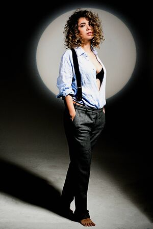 Girl with curly hair in a beam of bright light (gobo mask) in a linen blue shirt on a white background Standard-Bild - 138033092