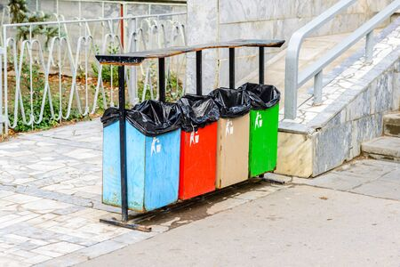 Bins for separate garbage collection at the exit from the store in the backwoods against the background of steps from the fragments of marble