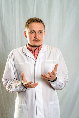 A man, a young doctor, he's annoyed and surprised. He holds the open palms of his hands in front of his chest as a symbol of the desire to protect himself