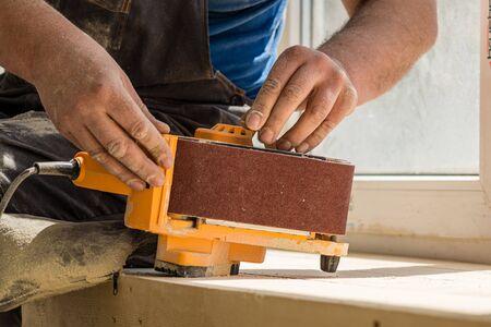 Carpenter's hands holding a belt sander against the background of the window. Replacing the sanding belt