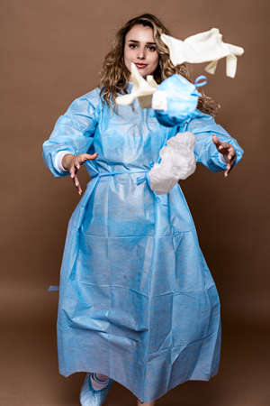 The physician removes a disposable surgical suit and throws it on the floor. The concept of protection from the external environment.