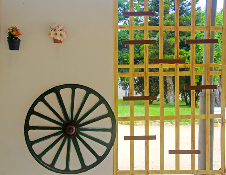 Cartwheel and flowers on the white wall and wooden grid
