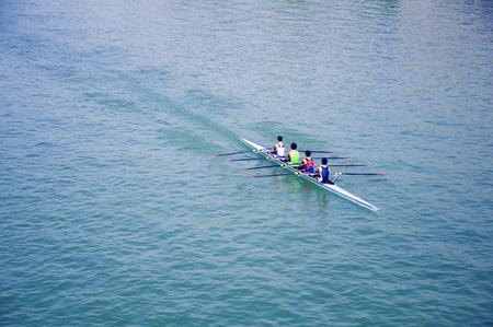 Four sportsmen on the canoe, blue river, autumn