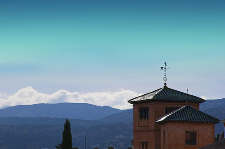 Two brick houses with roofs and weather vane, hills and mountains, blue sky, spring, Spain