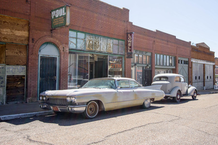 old cars on a small-town street in the ghost town of Lowell in Arizona Editorial