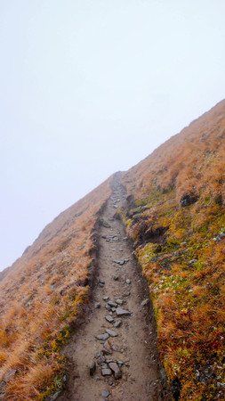 hiking path: a hiking path leading into a foggy abyss in the Swiss Alps
