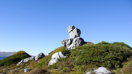 a natural rock formation in the form of a seated man on the summit of a peak in the Swiss Alps