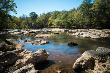 carolina: a river with low water and many rocks in the foreground and forest behind Stock Photo