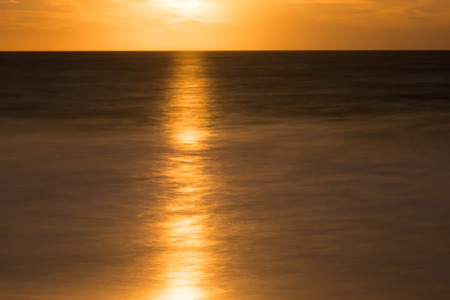 reflection of a full moon rising over the ocean