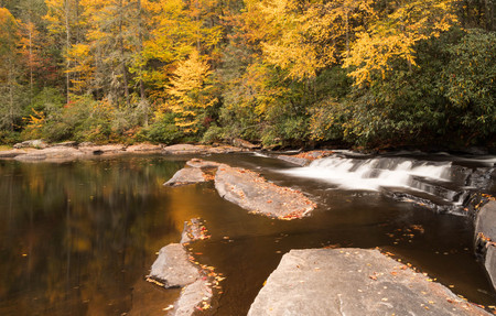 refelction: small waterfall with rocks in the foreground and fall foliage in the back