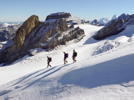 mountain guide and clients descending from a summit in the Bernese Oberland in Switzerland Stock Photo