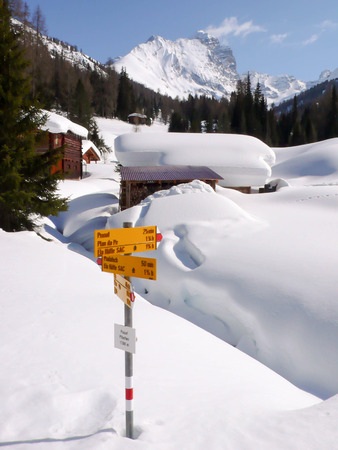 sign post: a small alpine village and sign post in deep winter in the Swiss Alps with Piz Ela in the background