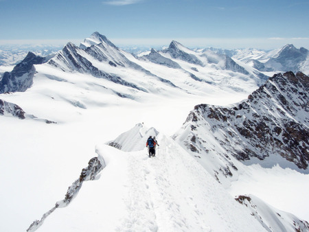 a panoramic view of the Bernese Alps in Switzerland with mountain climbers in the foreground