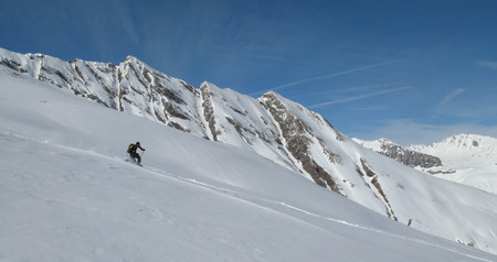 telemark skier on a fast descent in the fresh powder snow of the Swiss Alps Stock Photo