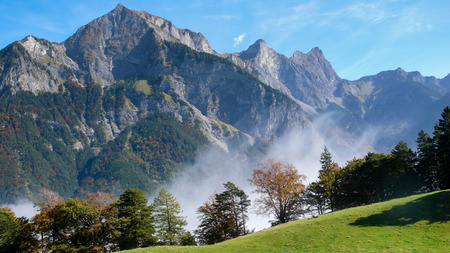 view of the Swiss Alps near Maienfeld during fall with fog in the valley and mountain peaks in the background