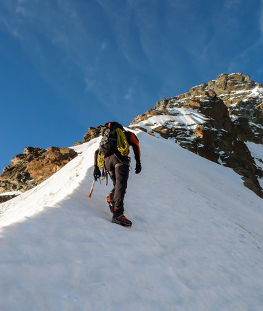 expose: mountain climber on a north face route in the Swiss Alps near Zermatt
