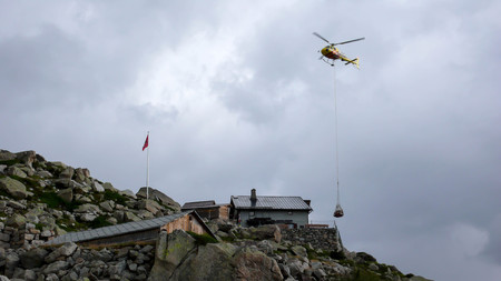 mountain hut: helicopter on a transport flight delivering a payload of goods to a remote mountain hut in the Swiss Alps