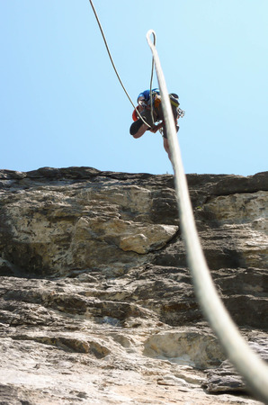 rappel: a rock climber rappelling off a steep limestone face in the Swiss Alps with rope in the the foreground Stock Photo