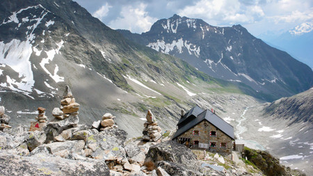 mountain hut: a mountain hut with many cairns in the foreground in the Swiss Alps