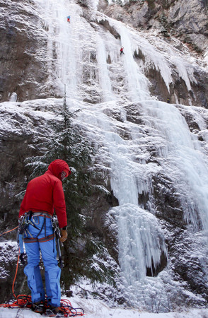 ice climber belays partner on an ice fall in Sottoguda in Italy