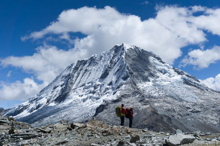 nevado: two hikers on a summit in the Cordillera Blanca in Peru with a view of Ranrapalca