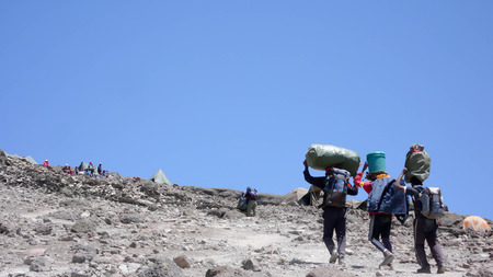 sherpa: porter carrying heavy loads near the high camp on Kilimanjaro in Tanzania