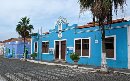 the Main Street in Tarrafal on Santiago Island in Cape Verde with a blue house in the foreground Stockfoto