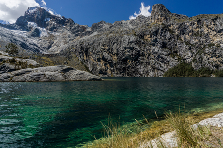 nevado: turquoise clear mountain lake with rocky and snow mountains in the Andes in Peru near Huaraz