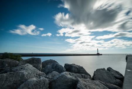 온타리오 호에 토론토 근처 Oakville에서 전경에서 신호 빛과 바위 해안 가진 항구 스톡 콘텐츠