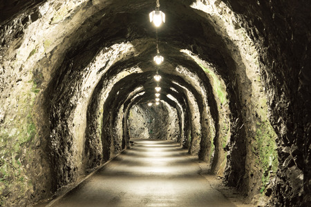 impressive old tunnel with sparse lighting in a mountain in the Swiss Alps